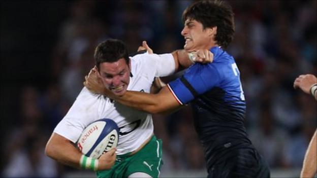 Irish centre Paddy Wallace is tackled by David Skrela in Bordeaux