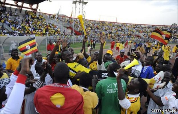 Fans of Uganda's Cranes hoist Andy Mwesigwa aloft after an early qualifying draw against Kenya