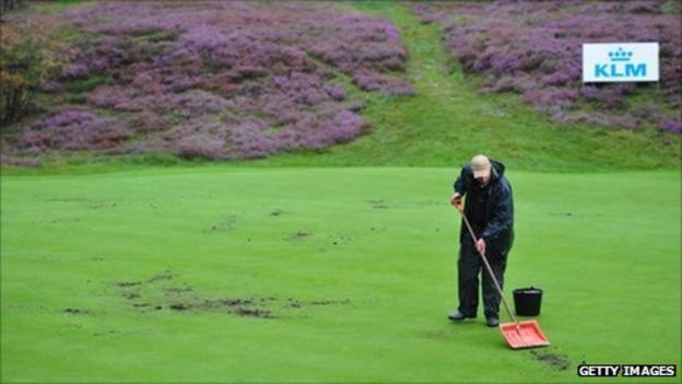 A greenkeeper repairs a green at Hilversum