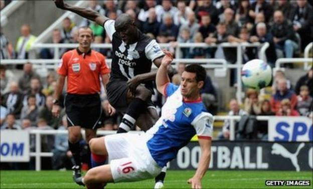 Demba Ba of Newcastle scores his team's opening goal past Scott Dann of Blackburn