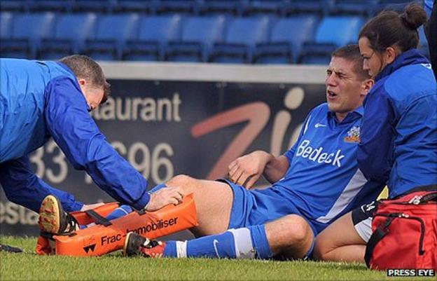 Mark Haughey receives medical attention after breaking his leg at Mourneview Park
