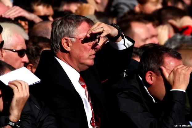 Sir Alex Ferguson shields his eyes from the sun