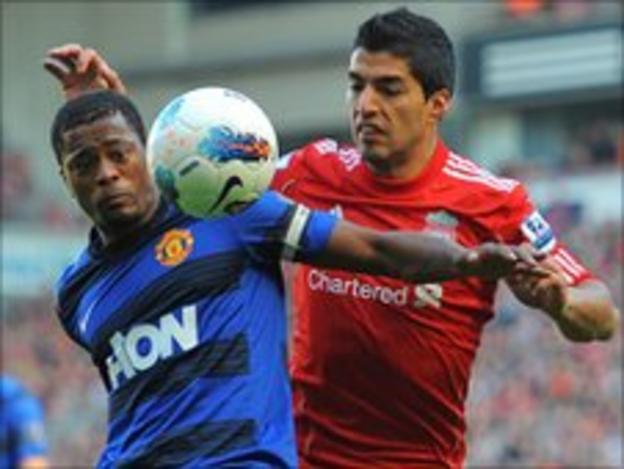 Liverpool striker Luis Suarez vies with Manchester United's Patrice Evra