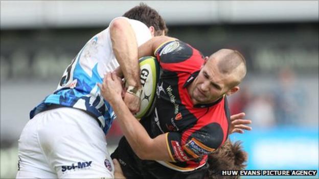Dragons' Martyn Thomas is tackled by Matt Carraro and Tom Heathcote