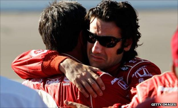 Dario Franchitti hugs a crew member on hearing of Dan Wheldon's death