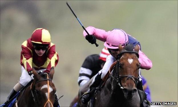 Jockey uses a whip at Brighton races