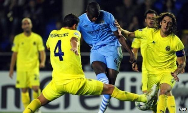 Manchester City's Yaya Toure shoots to score next to Villarreal's Argentine defenders Gonzalo Rodriguez (right) and Mateo Musacchio
