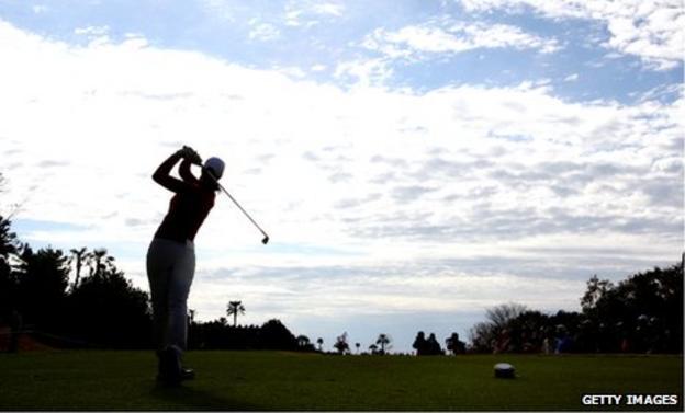 A female golfer tees off