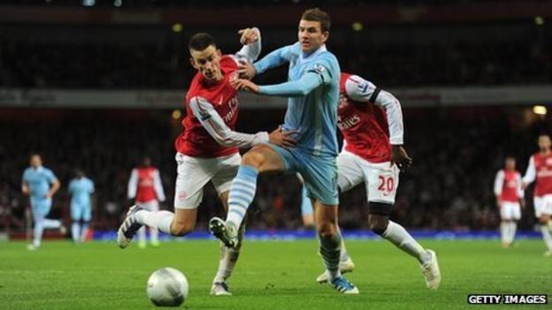 Manchester City's Edin Dzeko and Arsenal's Laurent Koscielny