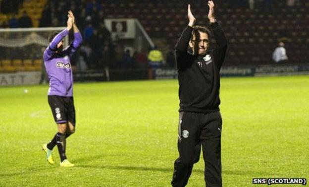 Pat Fenlon salutes the band of travelling Hibs fans at Fir Park