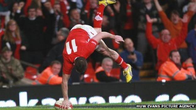 Wales wing Shane Williams cartwheels over the try line against Australia