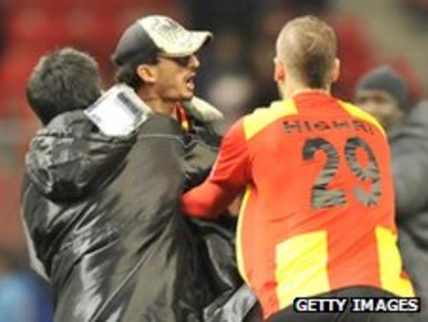 Esperance fan is restrained after running onto the pitch at the Club World Cup