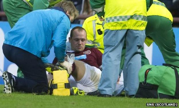 Hearts defender Jamie Hamill receives treatment on his injured ankle