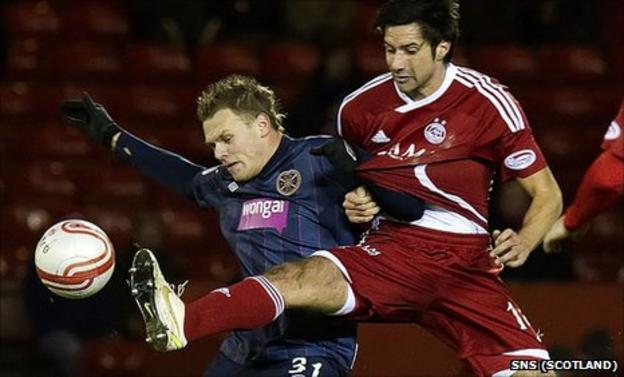 Adrian Mrowiec of Hearts at Aberdeen's Rory Fallon