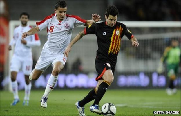 Cesc Fabregas of Catalonia (R) and Khaleo Korbi of Tunisia fight for the ball during the friendly between Catalonia and Tunisia