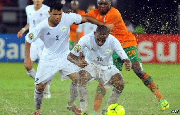 Libya and Zambia players struggle for the ball in rain-soaked Bata