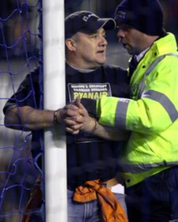 A fan handcuffs himself to a goalpost delaying the game by five minutes