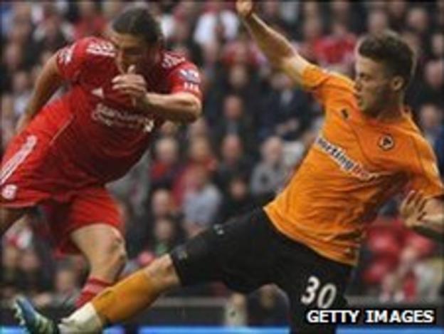 Matt Doherty slides in on Liverpool's Andy Carroll