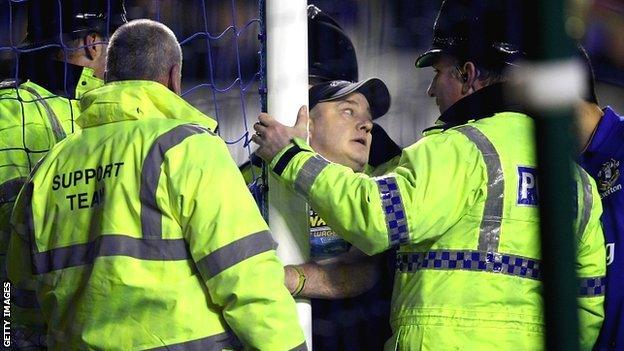 A spectator handcuffs himself to a goalpost during Everton's match with Manchester City at Goodison Park