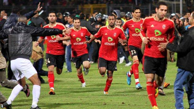 Players run for safety as violence erupts in the match between Al-Masry and al-Ahly