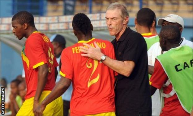 French coach Michel Dussuyer gives midfielder Pascal feindouno a pat during Guinea's group game against Botswana