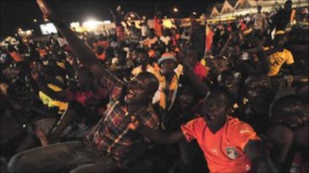 Ivorian fans celebrate an Elephants goal as they watch on a big screen in Abidjan
