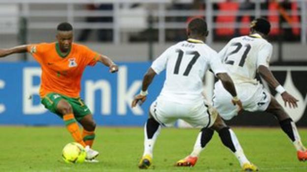 Zambia's Rainford Kalaba (L) runs at Ghana's Lee Addy (C) and John Boye (R)