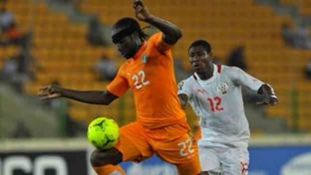 Ivory Coast defender Sol Bamba (L) evades a tackle by Burkina Faso's Prejuce Nakoulma