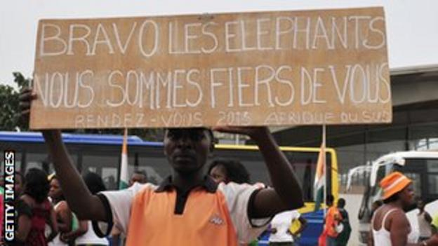 An Ivory Coast fan holds a sign which says he and his colleagues are proud of their team