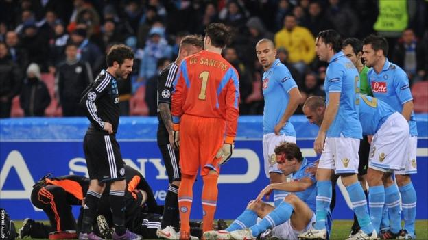 """Chelsea's Ivorian forward Didier Drogba (L) is treated after collidig with Napoli""""s Argentine defender Hugo Armando Campagnaro (R) during the Champions League round of 16 first leg football match, Napoli vs Chelsea at San Paolo stadium in Naples"""