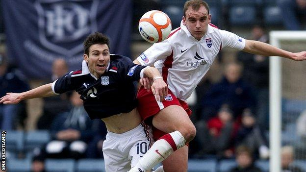 Dundee's Carl Finnigan goes head-to-head with Grant Munro (right)