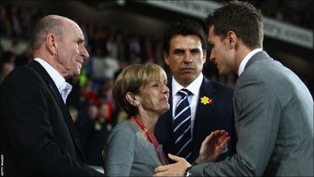 Wales captain Aaron Ramsey greets Gary Speed's parents Roger and Carol ahead of the Gary Speed Memorial Match in Cardiff under the watchful eye of his manager Chris Coleman