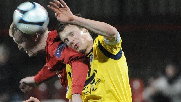 Crusaders striker Jordan Owens gets to the ball ahead of Evan McMillan