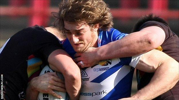 Liam Harrison for Barrow tackled by North Wales Crusaders players