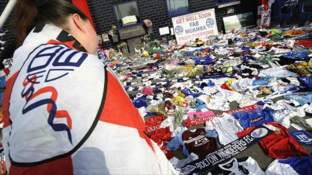 A woman looks at tributes to Bolton Wanderers' Fabrice Muamba outside their Reebok stadium