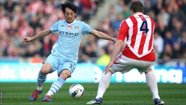 Manchester City's David Silva and Stoke City's Robert Huth (right) battle for the ball