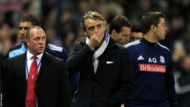 Roberto Mancini the manager of Manchester City walks off the pitch following his team's 1-1 draw against Stoke