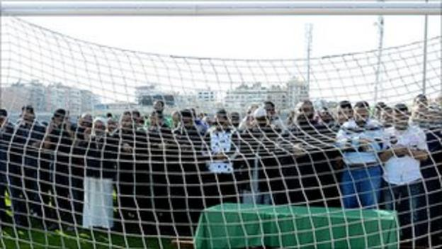Al-Masry fans pray behind the coffin of Belal Mamdouh, the 13-year-old boy who died on Friday
