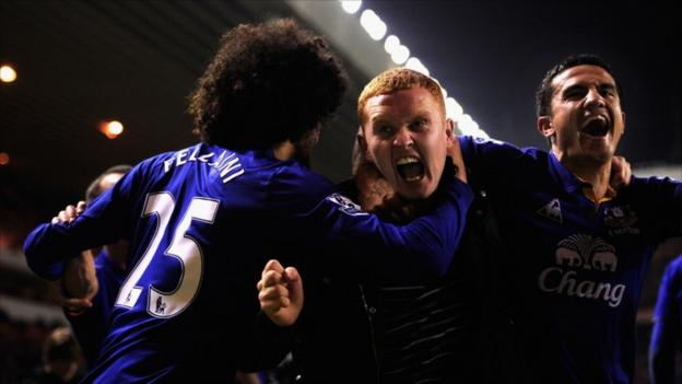 Everton player Tim Cahill (right) and a fan (centre) celebrate Everton's second goal