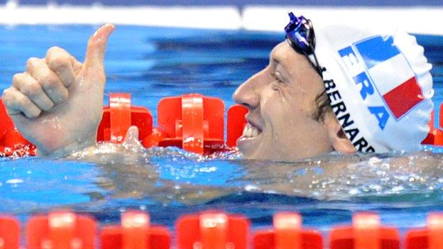Alain Bernard giving a thumbs up gesture in the pool