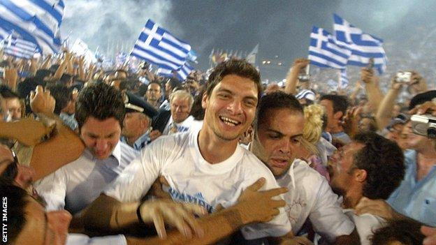 Greece's Angelos Charisteas is mobbed by fans on the team's triumphant return to Athens, 5 July, 2004