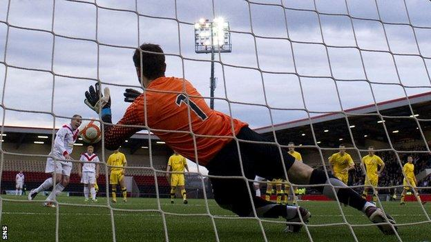 Kevin Cuthbert saves a penalty from Paul Lovering
