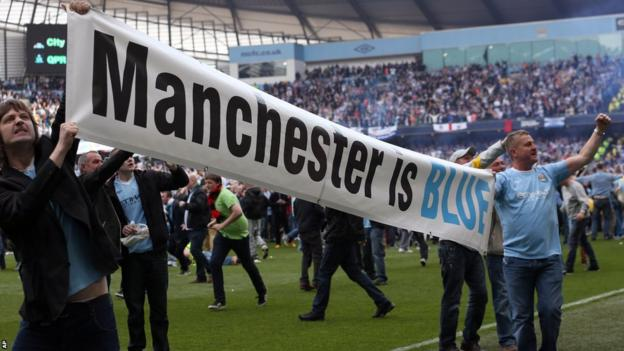 Manchester City fans celebrate on the pitch