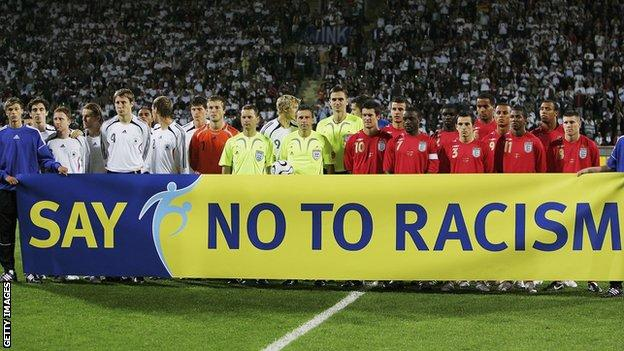 England players hold a 'Say No To Racism' banner in front of the cameras