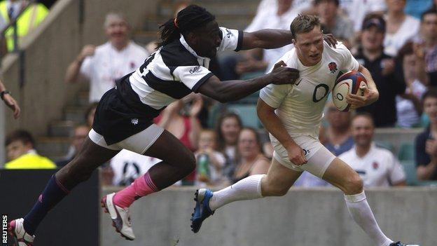 England wing Chris Ashton holds off the tackle of Paul Sackey to score his second try
