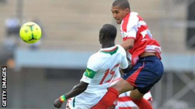 Liberia's Barshall Cele rises above new Senegal Papiss Demba Cisse, who missed an early penalty