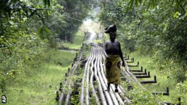 A woman walks along an oil pipeline in Warri, southern Nigeria