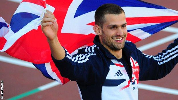 Robbie Grabarz holds the British flag aloft after winning high jump gold
