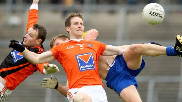 Armagh goalkeeper Philip McEvoy and Finnian Moriarty challenge for the ball with Niall Daly of Roscommon