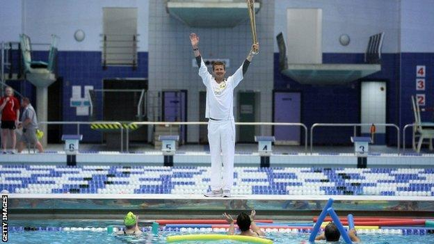 Former Olympian Steve Cram holds the Olympic Torch aloft at the Sunderland Aquatic Centre